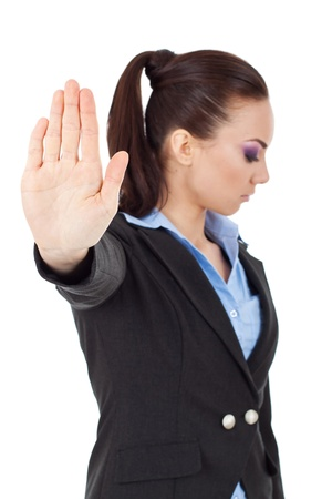veto: young business woman holding hand out to stop viewer. talk to the hand gesture looking away from the camera. isolated on white background