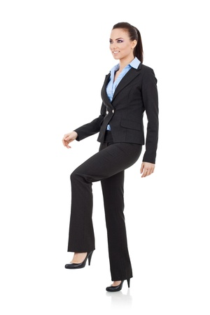 Young attractive business woman stepping on imaginary step and looking away from the camera, upwards, suggesting progress photo