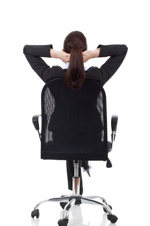 hands behind back: portrait of cute young business woman from behind dreaming, resting on office chair with hands behind her head