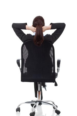 businesswoman suit: Retrato de mujer de negocios linda joven de detr�s so�ar, descansar en la silla de la oficina con las manos detr�s de la cabeza Foto de archivo