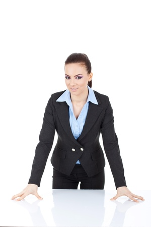 bossy: young business woman standing in front of the desk, leaning on it and smiling at the camera. isolated on white