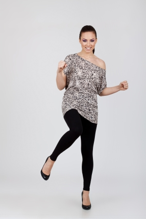 amazingly beautiful young woman wearing leopard blouse is standing with a leg raised ready to kick you while smiling. on gray background Stock Photo - 15738276