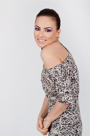 appealing young woman revealing a revealing shoulder and smiling shyly at the camera, on gray background Stock Photo - 15738350