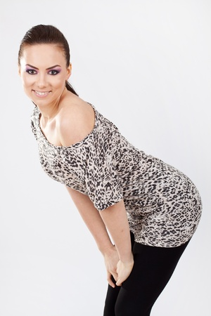 beautiful young woman emphasizing her amazing body, looking at the camera and smiling. bending and holding hands on knees, on gray background photo