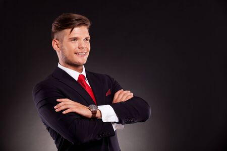 Handsome young business man standing with arms crossed and smiling, while looking away from camera. on dark background Stock Photo