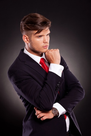 man side: angle view of a pensive young business man looking away from the camera, on a dark background