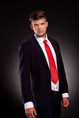 appealing attractive: attractive young business man posing on a dark background