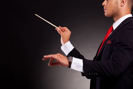 young musician: side view of a young business man conducting with a conductors baton, on a dark background
