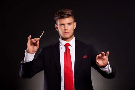 young business man conducting with a stick, while looking at the camera. on dark background photo