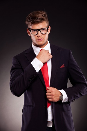 formal dressing: waist-up picture of a young business man fixing his tie and looking into the camera. on dark background