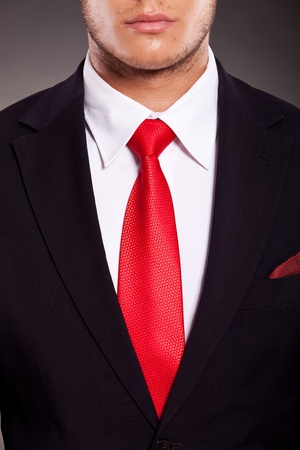 detail of young business mans suit with red tie, on dark background