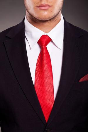 traje: detalle del traje de hombre de negocios de j�venes con corbata roja, sobre fondo oscuro Foto de archivo