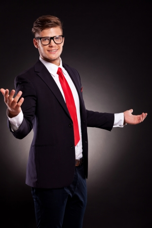 picture of a young business man welcoming you with a smile on his face. dark background photo
