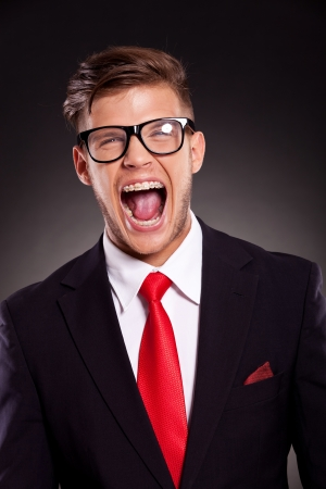 mouth  open: portrait of a young business man with eyeglasses shouting with mouth wide open, on dark background Stock Photo