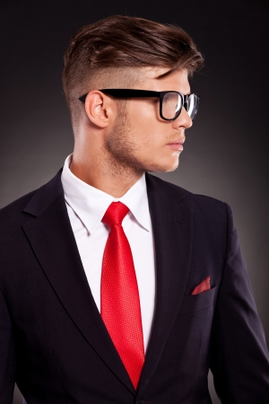 latin look: closeup picture of a young business man looking to his side, on dark background Stock Photo