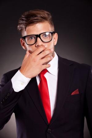 quiet adult: ritratto di un giovane uomo d'affari che copre la bocca con la mano per la sorpresa. su sfondo scuro