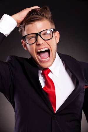 going crazy: portrait of a desperate young business man shouting and pulling his hair. over dark background