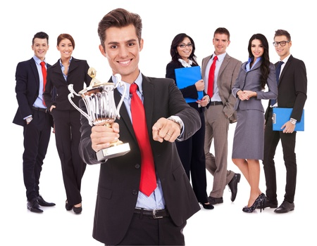victory stand: winning business team with leader holding a big trophy cup and pointing to you, on white background