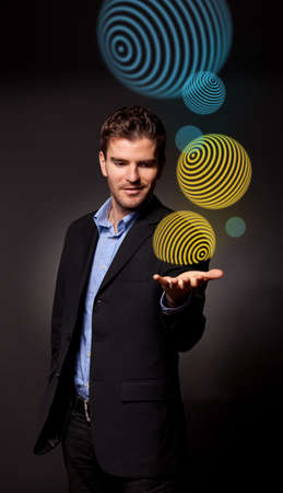 Young business man holding some spheres over his hand Stock Photo - 15992110