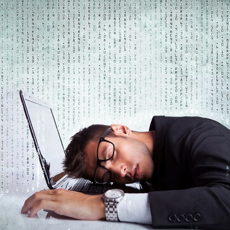 burdensome: Business man sleeping on a laptop computer on a background full of numbers Stock Photo