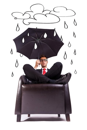 Image of a business man sitting in comfortable armchair with an umbrella in his hand - rainy days photo