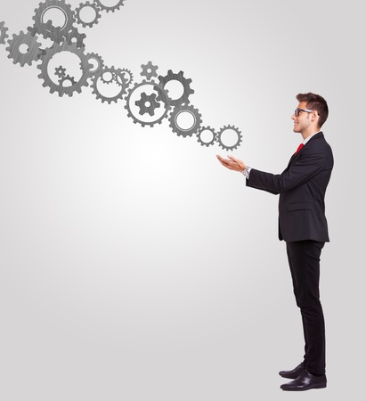 Business man holding some cog mechanisms in his hands Stock Photo - 16014386