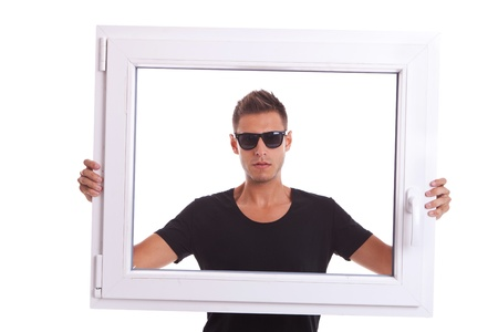 glazing: young man wearing sunglasses is holding a pvc window frame on white background