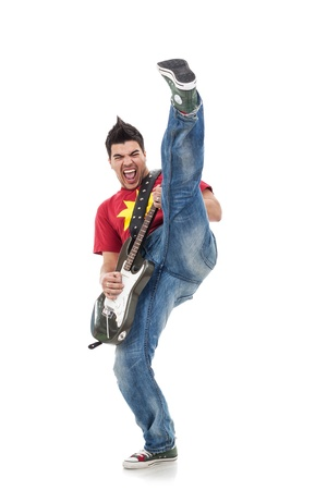 headbang: raging electric guitar player is kicking high in the air while performing. casual young man playing guitar and kicking Stock Photo