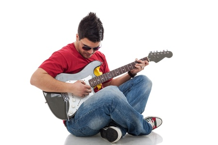 young casual man sitting with legs crossed and practicing on his electric guitar, on white background photo