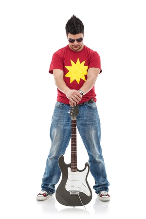 spread legs: full length picture of a young casual man holding a guitar between his spread legs and looking down Stock Photo