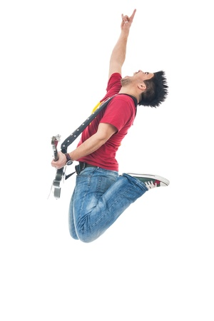 casual young rocker with electric guiar is  jumping and showing rock sign while shouting out loud, on a white background photo