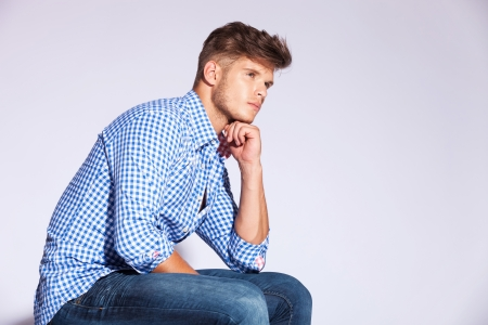 sitting down: side view of a casual fashion man sitting against gray background and looking away from the camera