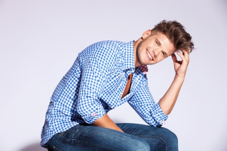 var�n: rubia modelo masculino sentado moda y riendo sobre fondo gris