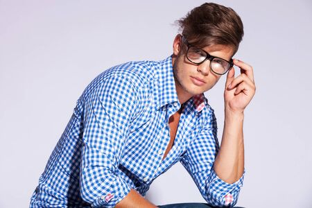 casual fashion male model holding his glasses and looking at the camera on gray background photo