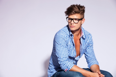 sitting down: cool fashion model sitting and looking to his right side on gray background