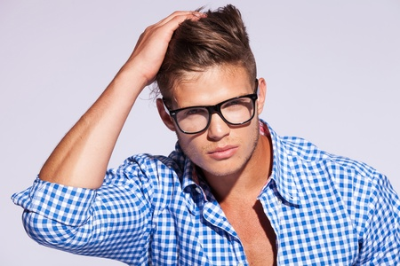 brown hair blue eyes: young casual fashion man wearing a shirt with eyeglasses on gray background