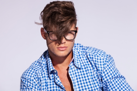 fashion man wearing glasses and his hair over his face on gray background