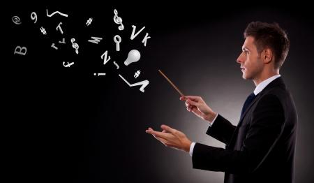 orquesta: Vista lateral de un hombre de negocios joven director con una batuta de un mont�n de s�mbolos
