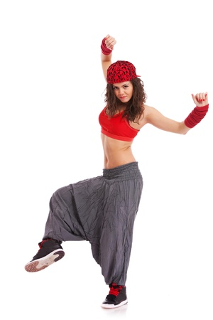 hip hop dance: modern woman street dancer posing on a white background with leg and arms raised