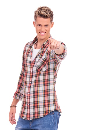 pointing fingers: happy young handsome casual man pointing and looking at the camera on white background