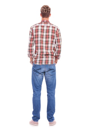 persona de pie: Vista trasera de un hombre ocasional joven de pie con las manos en los bolsillos