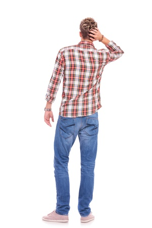 hands behind head: back view of a confused young casual man with his hand on the back of his head. isolated on white