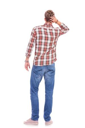 persona confundida: Vista posterior de un confuso casual hombre joven con la mano en la parte posterior de la cabeza. aislado en blanco
