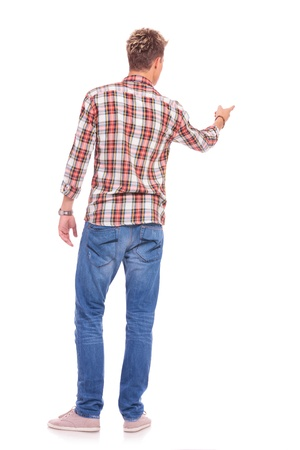 rear view of a young casual man pointing at something in front of him, on white background Stock Photo - 16109543