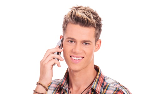 closeup portrait of a young casual man speaking on the phone and smiling to the camera, isolated on white background photo