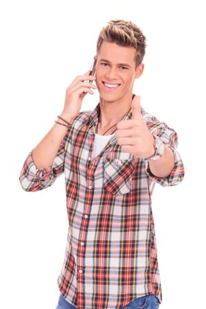 appealing: appealing young casual man showing thumbs up gesture while speaking on the phone Stock Photo