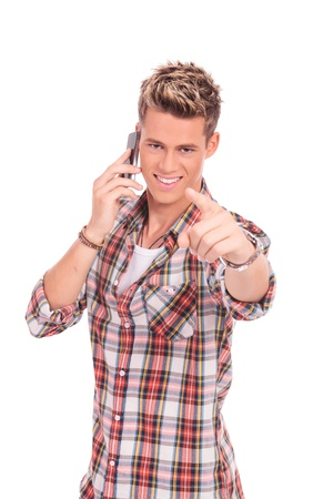 close up picture of a young casual man speaking on the phone and pointing at you Stock Photo - 16109737