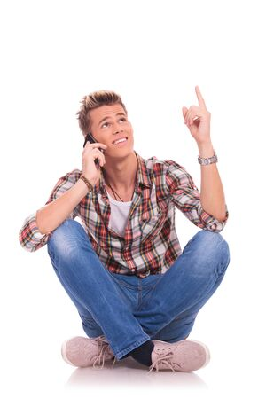 young man sitting on the floor, legs folded, talking on the phone, pointing and looking up. isolated on white  photo