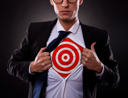 Young business man showing a target under his shirt on dark background Stock Photo - 16109746