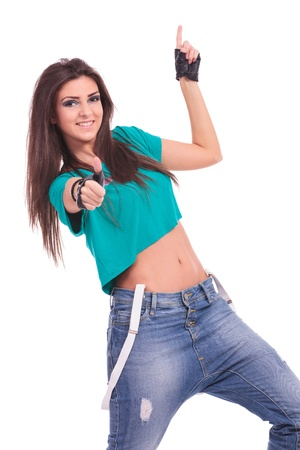 merry dancers: beautiful young woman dancer smiling at the camera, showing thumb up sign and pointing upwards. on white background
